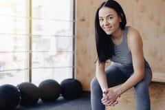 Moça no sportswear em um gym em um fundo simples, em um tema da aptidão e no esporte imagem de stock royalty free