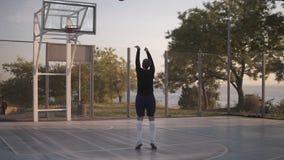 A moça no sportswear pratica jogar uma bola na aro Jogador de basquetebol profissional que exercita na corte filme