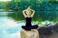A moça no t-shirt e em caneleiras pretos senta-se em uma pedra na pose dos lótus perto do lago imagens de stock