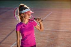 Moça no tampão e no sportswear à moda com a raquete no ombro no fundo da luz do sol Jogador de tênis fêmea sobre fotos de stock royalty free