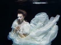 Moça no vestido branco longo subaquático Foto de Stock Royalty Free