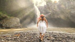 Moça no vestido e em Straw Hat Runing à cachoeira de Tegenungan e em aumentar brancos acima os braços Curso despreocupado 4K do e vídeos de arquivo