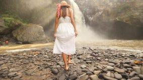 Moça no vestido e em Straw Hat Walking brancos à metragem Slowmotion despreocupada do curso 4K do estilo de vida da cachoeira de  filme