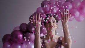A moça no vestido roxo joga confetes acima vídeos de arquivo