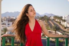 Moça no vestido vermelho que aprecia no balcão do hotel imagens de stock