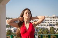 Moça no vestido vermelho que aprecia no balcão do hotel foto de stock