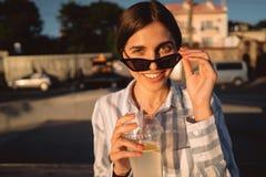 Moça nos óculos de sol com um vidro da limonada foto de stock