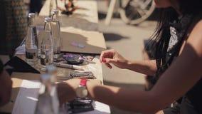 A moça nos óculos de sol explica algo aos povos Cartões na tabela Dia ensolarado do verão festival vídeos de arquivo