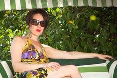 Moça nos óculos de sol que sentam-se no fundo do verde do verão fotos de stock