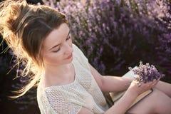 Moça nos campos da alfazema com o ramalhete das flores fotografia de stock royalty free