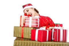 Moça nos dentes dos chapéus de Santa que tentam abrir uma caixa com um presente Imagem de Stock Royalty Free