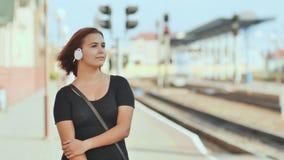 A moça nos fones de ouvido brancos com prazer escuta a música na perspectiva da estação de trem vídeos de arquivo
