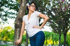 Moça nos vidros e na roupa ocasional no parque na natureza Fotografia de Stock