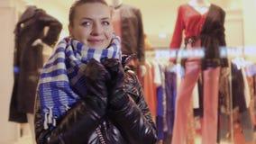 A moça olha em torno dsi mesma e vai na compra na loja moderna video estoque