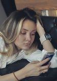 A moça olha a reclinação do telefone, sustentando sua cabeça em sua mão Foto de Stock