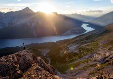 A moça olha sobre um lago nas montanhas no por do sol Fotos de Stock