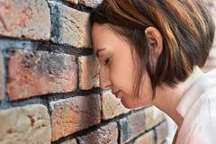 A moça pôs sua cabeça à parede de tijolo, conceito do problema Fotos de Stock Royalty Free