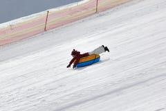 Moça para baixo no tubo da neve na estância de esqui no dia de inverno ensolarado imagens de stock royalty free