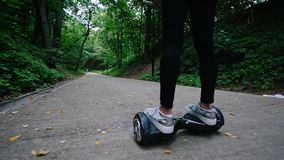 A moça passa o tempo no parque, montando um giroscópio Em torno das árvores Uma pessoa desconhecida vem encontrar-se vídeos de arquivo