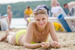 A moça pegarou a areia que encontra-se em seu estômago no Sandy Beach Fotos de Stock