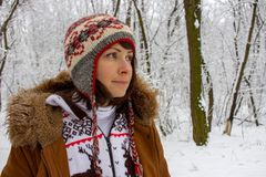Moça pensativa no desgaste acolhedor feito malha no tempo nevado do inverno da floresta do inverno e no conceito da roupa Fundo d imagem de stock