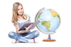 moça pequena bonito com tabuleta e globo Estudante que usa a tecnologia moderna na geografia de ensino foto de stock royalty free