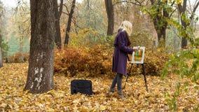 A moça pinta uma imagem no parque do outono imagem de stock