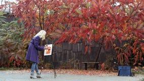 A moça pinta uma imagem no parque do outono fotos de stock