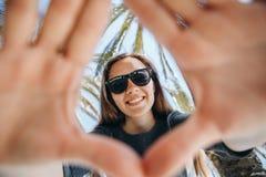 Moça positiva, ou um turista feliz em um fundo das palmeiras e do céu azul em um país quente Fotografia de Stock