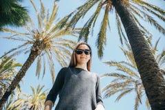 Moça positiva, ou um turista feliz em um fundo das palmeiras e do céu azul em um país quente Imagem de Stock