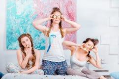 A moça positiva que tem o divertimento em casa que senta-se na cama e faz Imagens de Stock