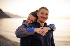 Moça que abraça seu noivo feliz de atrás imagens de stock