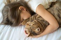 Moça que afaga o gato que encontra-se na cama fotos de stock