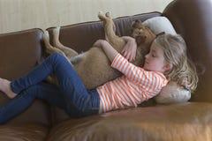 Moça que afaga seu cão de estimação em casa Foto de Stock