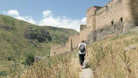 A moça que anda e vê a fortaleza de Khertvisi - Geórgia video estoque
