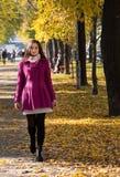 Moça que anda no parque na cidade no outono Imagem de Stock