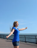 Moça que aprecia o sol e o vento pelo oceano Imagens de Stock