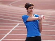 Moça que aquece-se na pista de atletismo Fotografia de Stock
