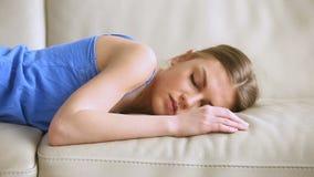 Moça que cai no sofá, adormecido desmaiado de encontro, sentindo esgotado filme