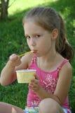 Moça que come fora o gelado Fotografia de Stock
