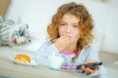 Moça que come o petisco que guarda o controlo a distância fotografia de stock royalty free