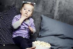 Moça que come a pipoca com vidros 3D Imagem de Stock