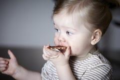 Moça que come um petisco, messily Foto de Stock Royalty Free