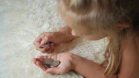 Moça que conta moedas, dinheiro da economia da criança Criança que conta suas economias Criança pequena que conta o dinheiro video estoque
