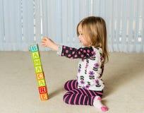 Moça que cria a torre de Obamacare dos blocos de madeira Fotografia de Stock
