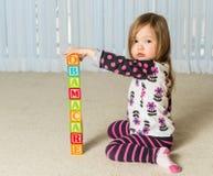 Moça que cria a torre de Obamacare dos blocos de madeira Fotos de Stock