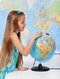 Moça que encontra lugares em um globo Imagens de Stock
