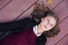 Moça que encontra-se no de madeira Fotografia de Stock Royalty Free