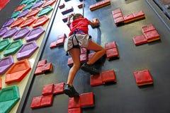 Moça que escala em uma parede de escalada Foto de Stock