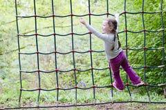 Moça que escala no quadro líquido da corda no parkground exterior da aventura da floresta fotos de stock royalty free
